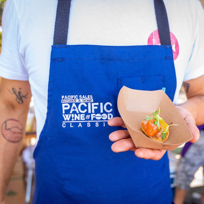 Pacific Wine and Food Classic man in blue apron holding snack in brown paper take out container