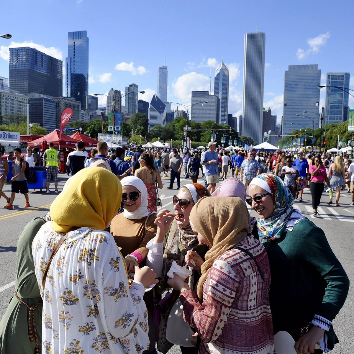 Taste of Chicago muslim women eating street foot with chicago skyline in background
