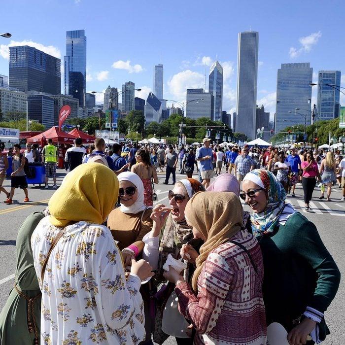 Taste of Chicago muslim women eating street foot with chicago skyline in background