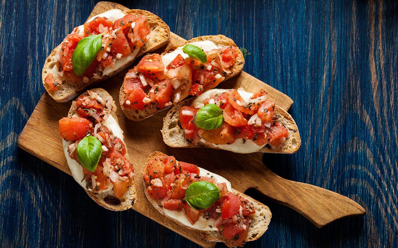 Italian bruschetta (tomato mozzarella basil bread) on a cutting board