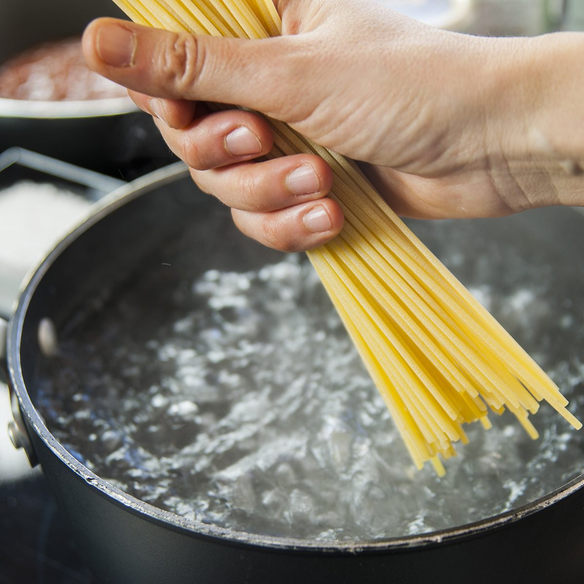 Cooking spaghetti in a pot with boiling water;