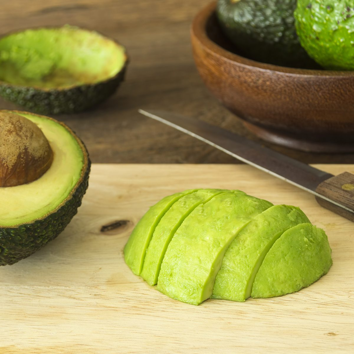 avocado and Sliced avocado slices on wooden board