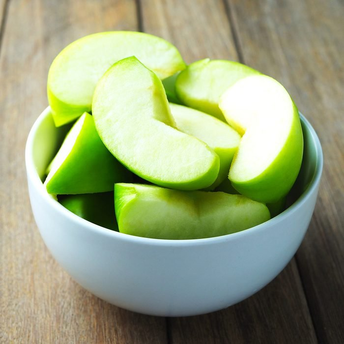 Close up of a bowl of apple slices on a wooden table.