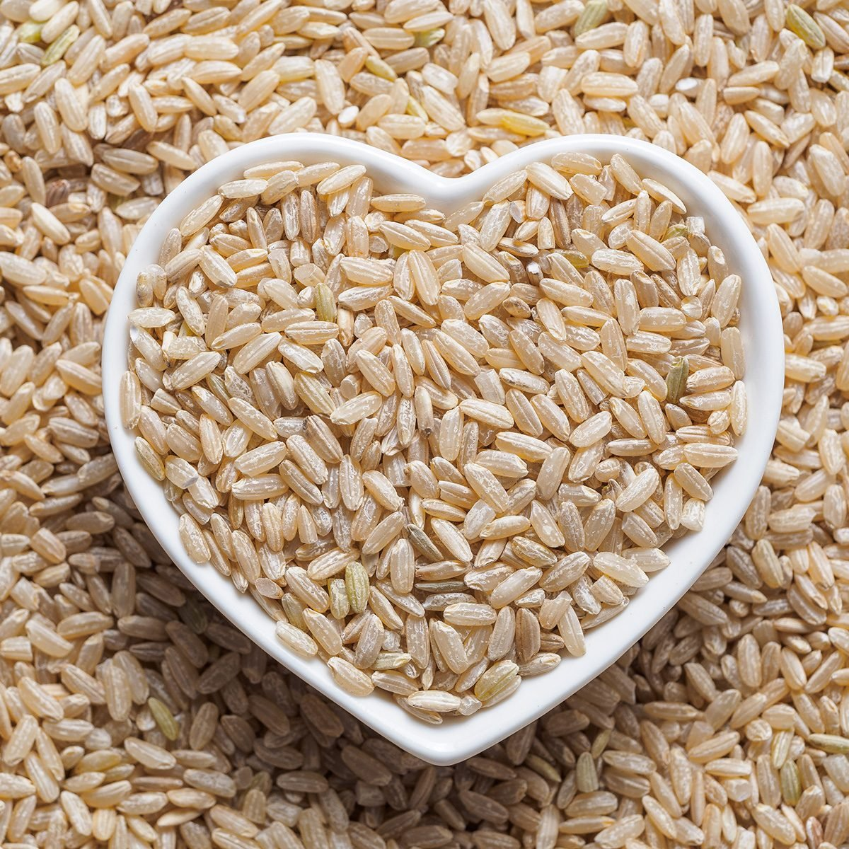 Brown rice in heart-shaped bowl on rice background.