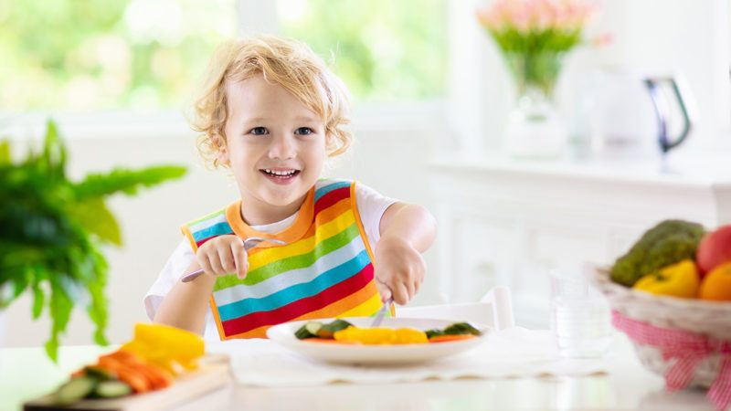 Child eating vegetables sitting in white high chair.