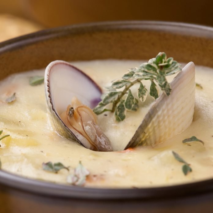 Bowls of hot delicious clam chowder garnished with fresh thyme, and multy grain crackers