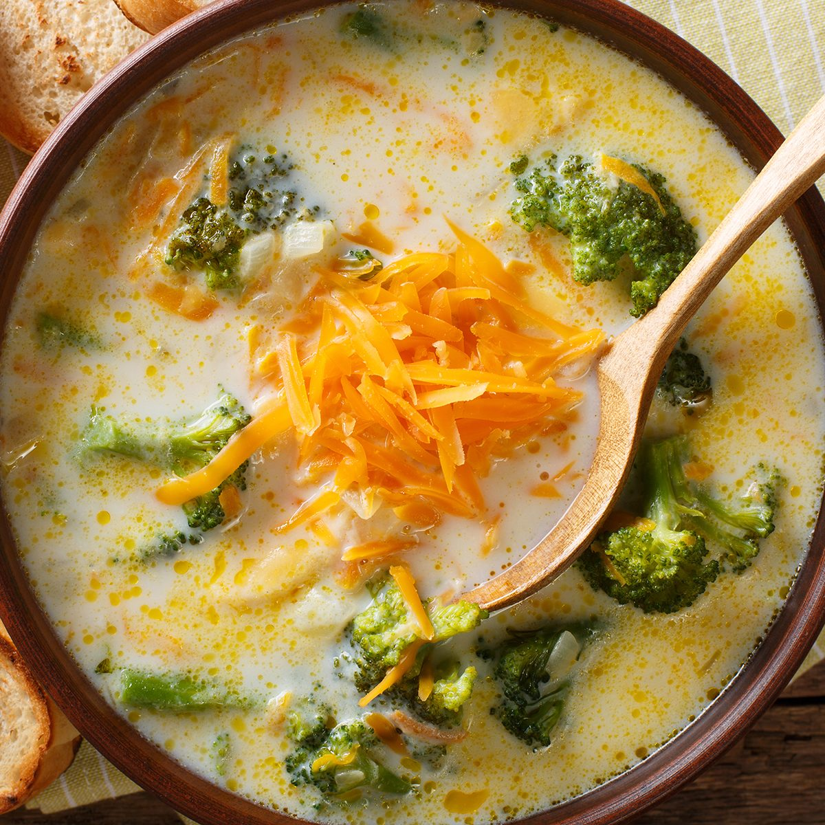 broccoli cheese soup served with toasted bread close-up in a bowl on the table. horizontal top view from above