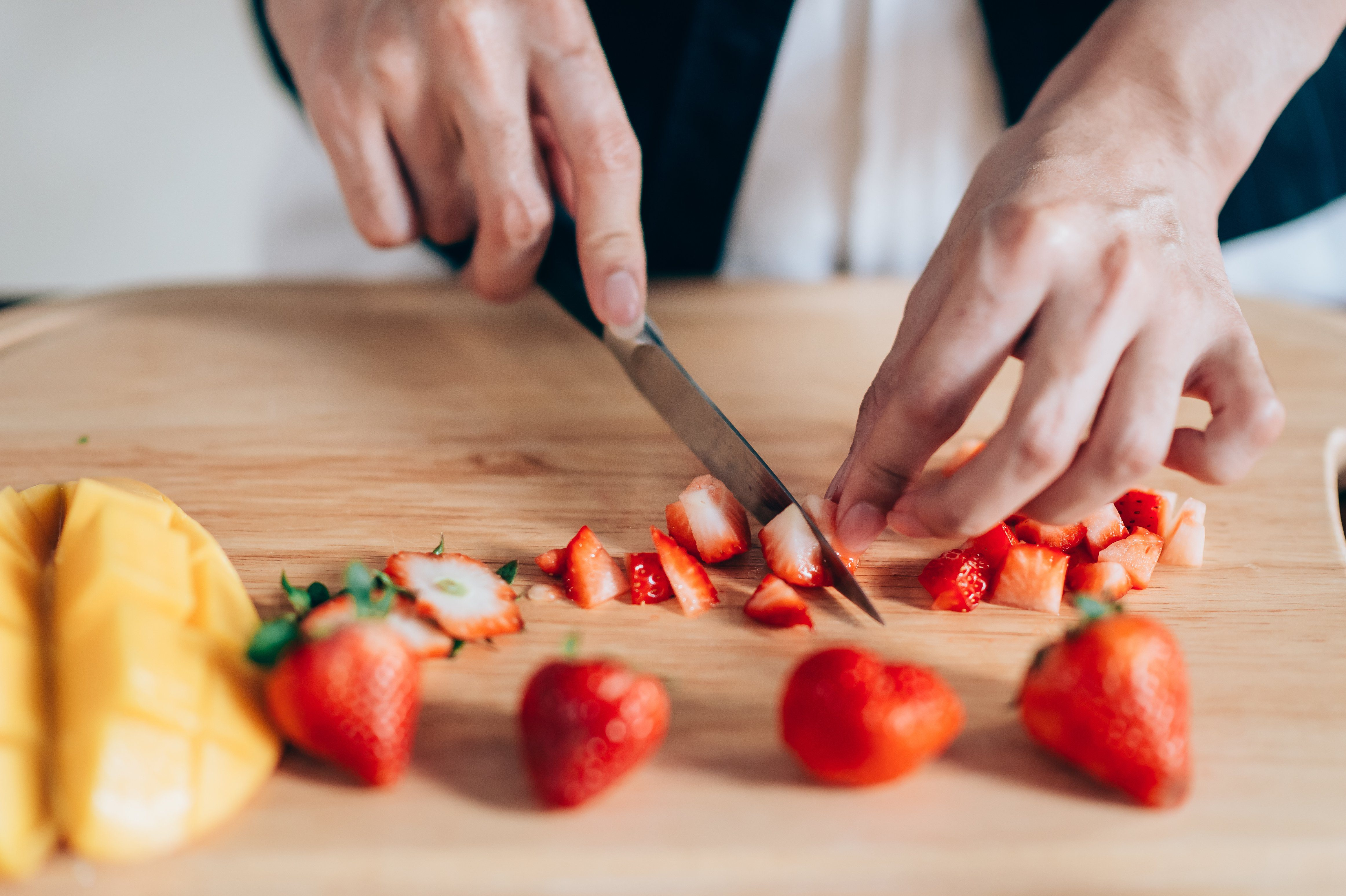 Chef Hand and Knife Slicing Fresh strawberry on wooden cutting board.