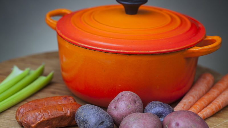Orange enamel dutch oven on wood cutting board with potatoes, carrots, chorizo & celery arrayed