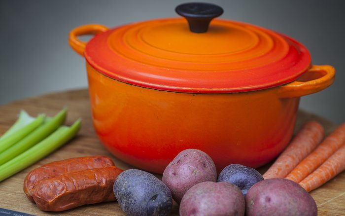 Orange enamel dutch oven on wood cutting board with potatoes, carrots, chorizo & celery arrayed