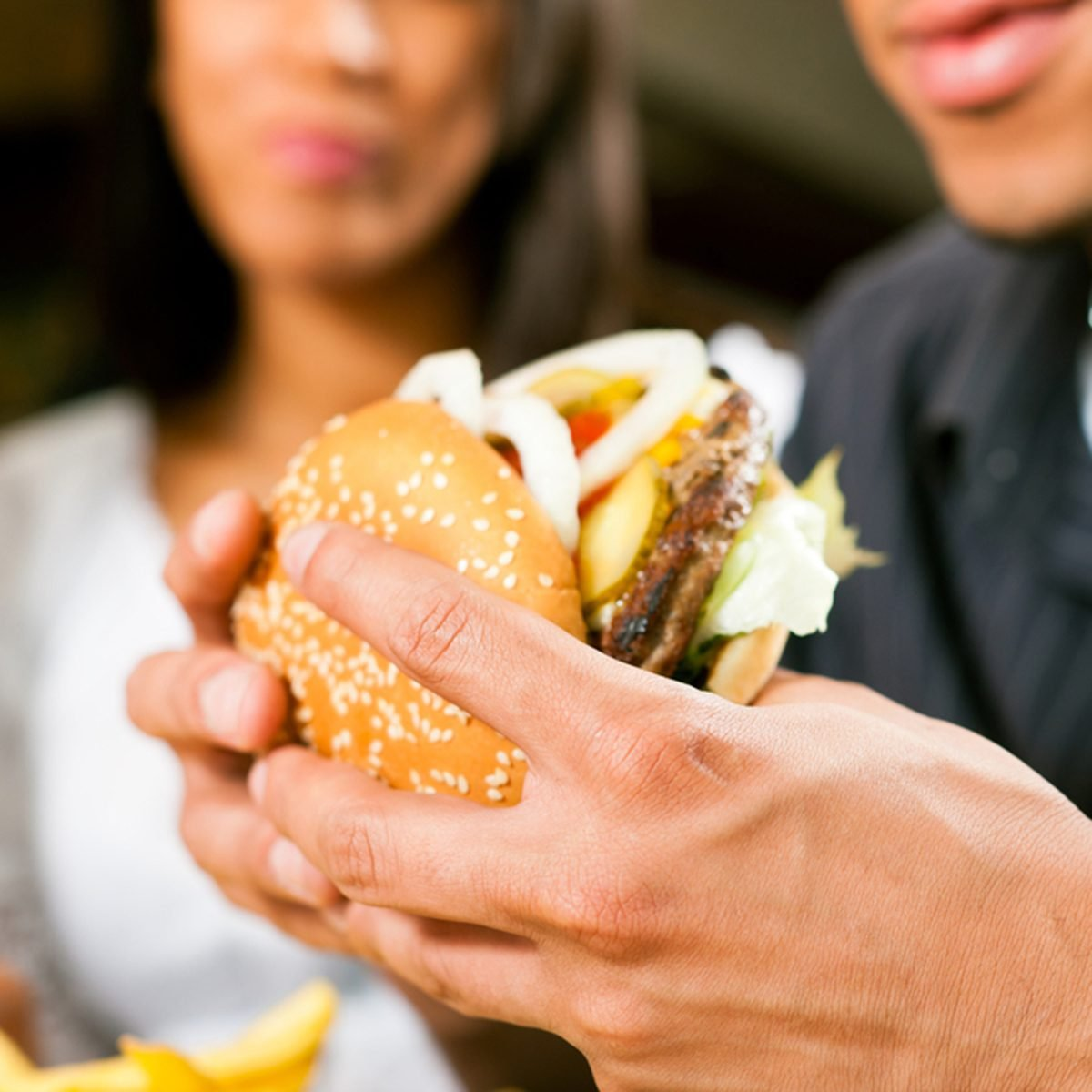 Happy man (African American) in a fast food restaurant eating a hamburger with his girlfriend