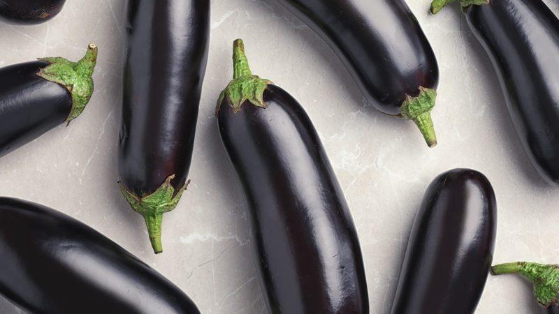 Raw ripe eggplants on light background