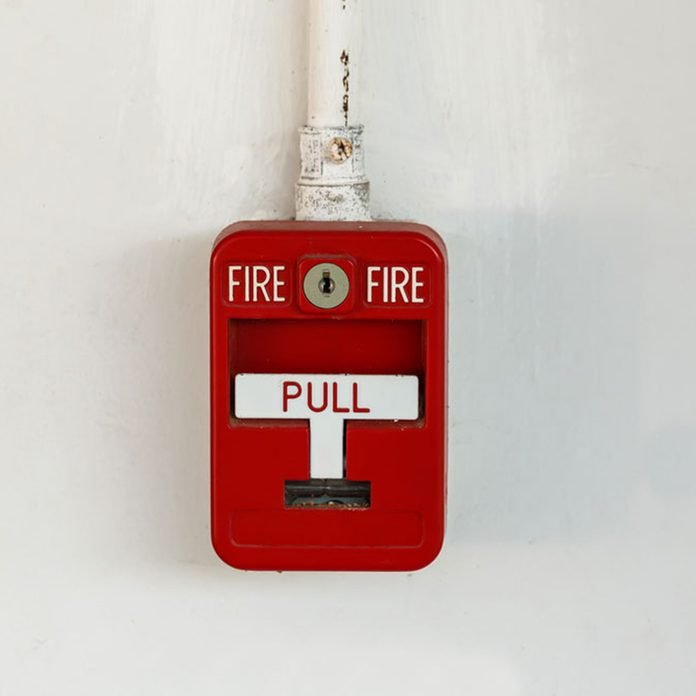 Old red box fire alarm isolated on white background
