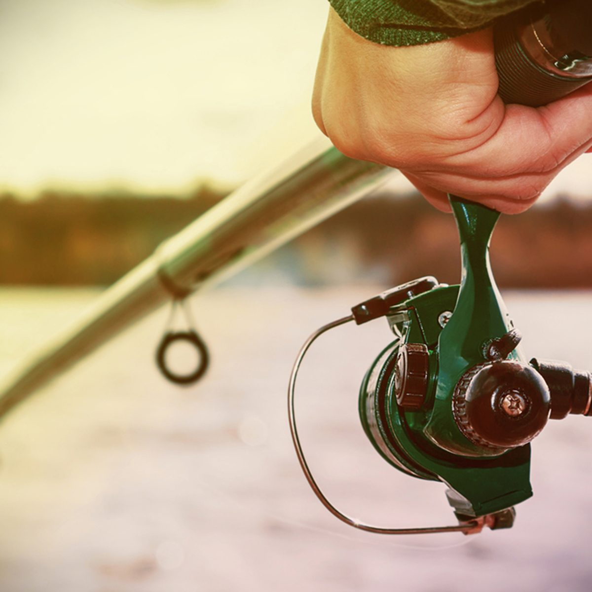 hand holding a fishing rod with reel.