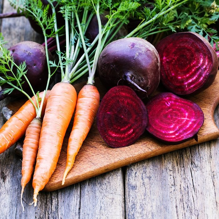 Fresh beet and carrots on wooden background