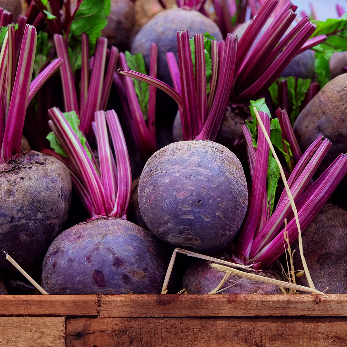 Fresh harvested beetroots in wooden crate, beets with leaves in the market