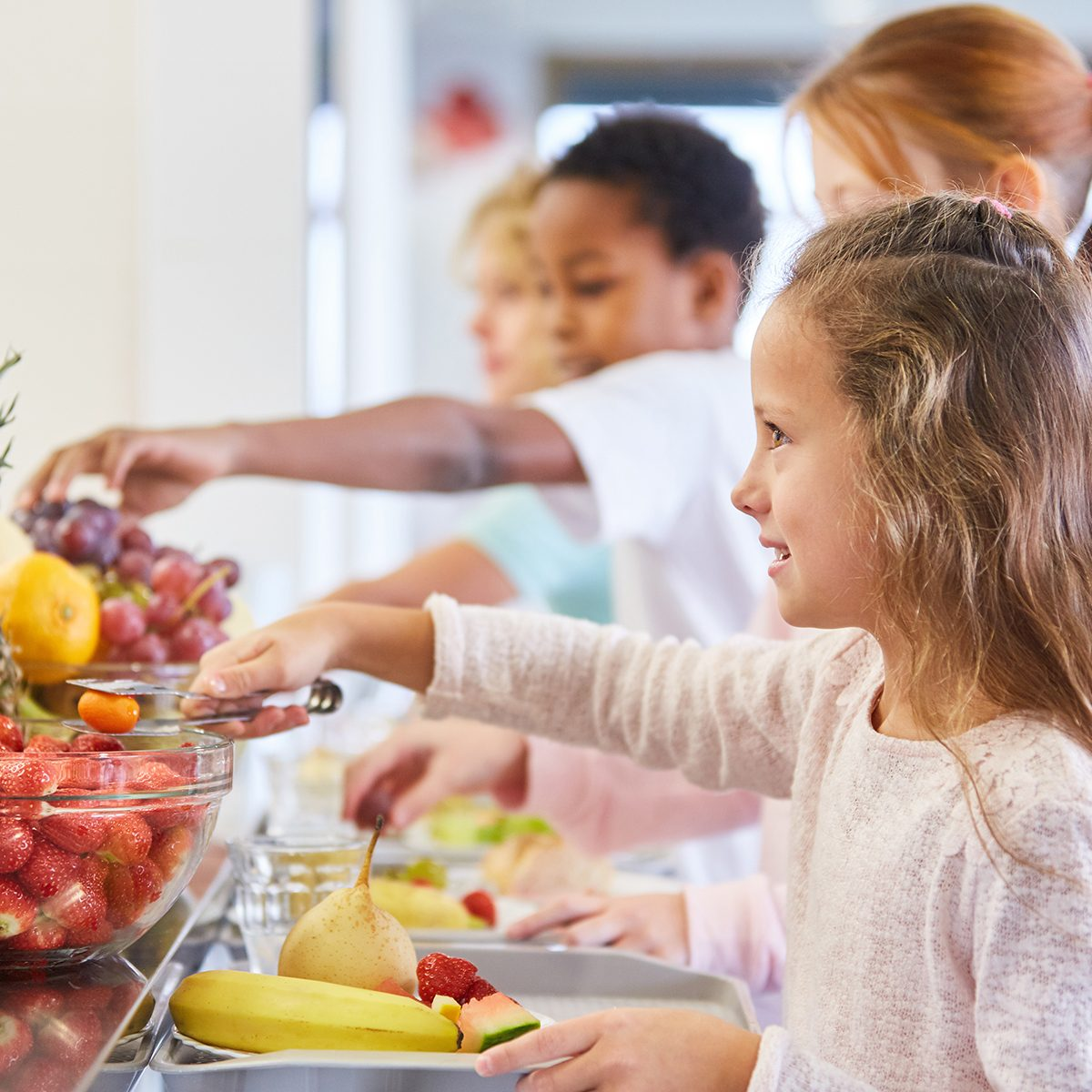 Girl and other kids at the fruit buffet at the cafeteria in elementary school
