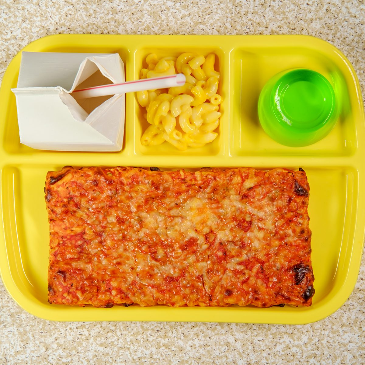 Grade school lunch tray with pizza with small carton of milk mac-n-cheese and green gelatin for dessert