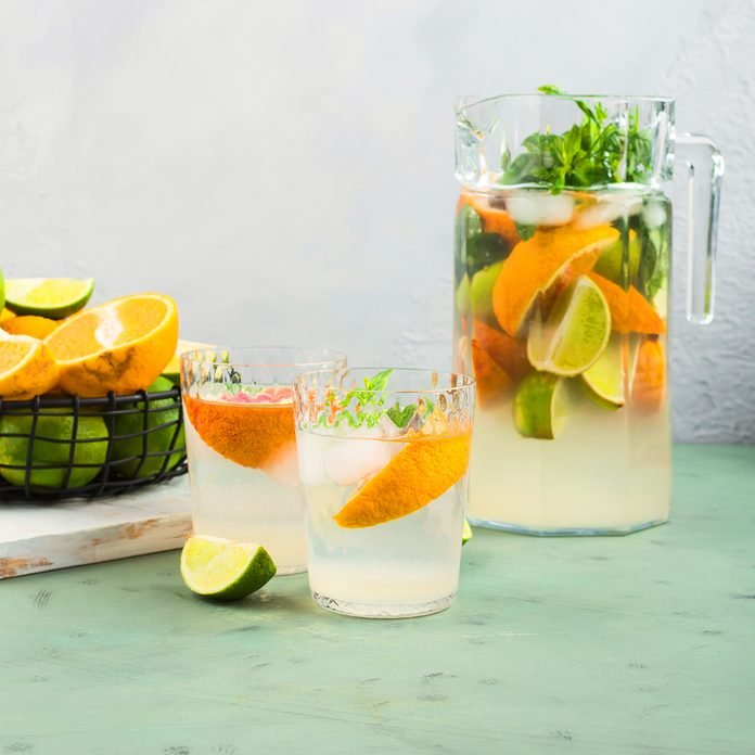 Fresh summer citrus lemonade with lime, mint, blood oranges and ice cubes in jar and glasses over green textured background.