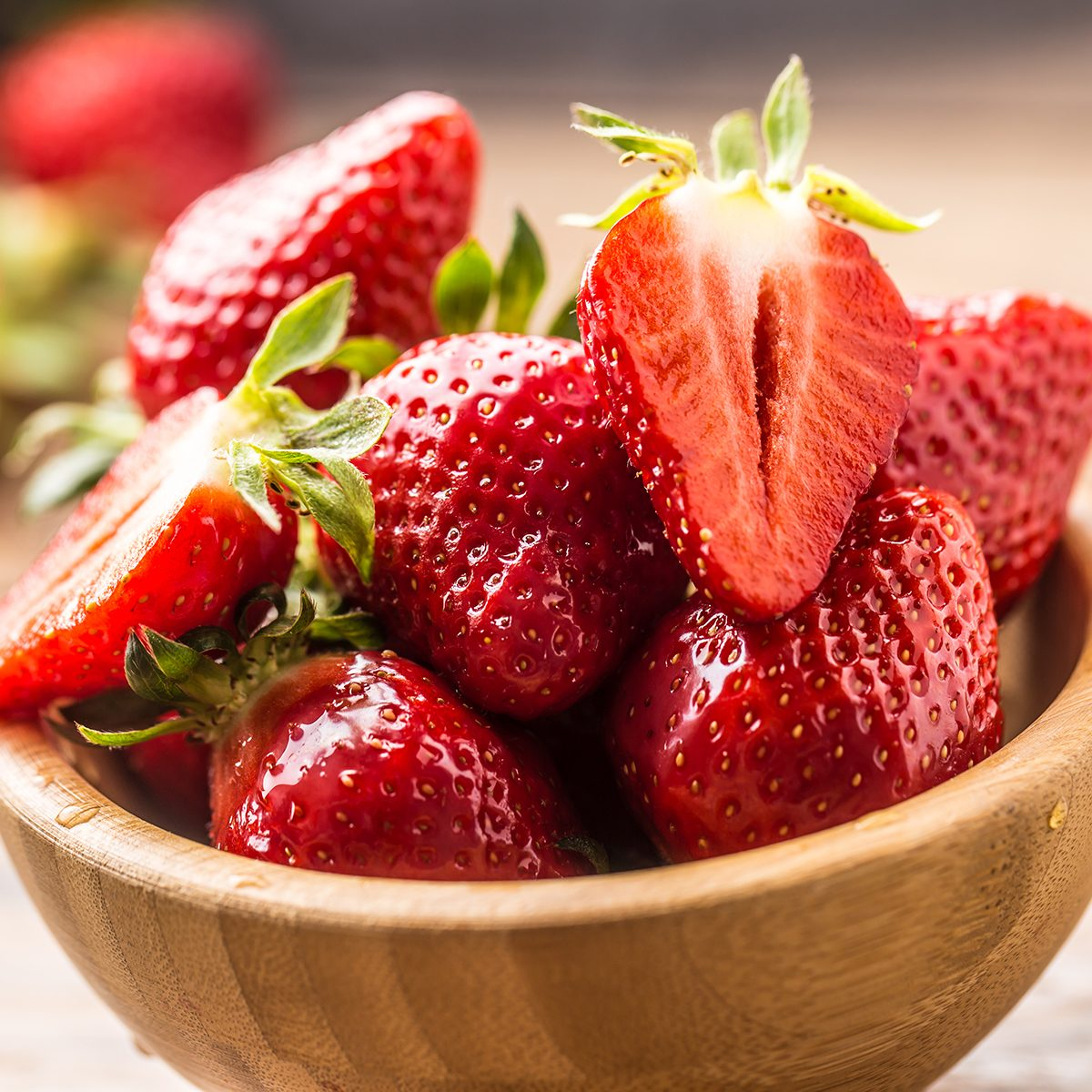 Juicy washed strawberries in wooden bowl on kitchen table.