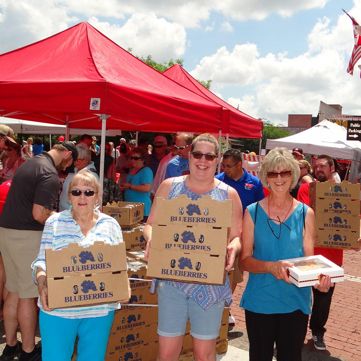 Ladies holding boxes of blueberries