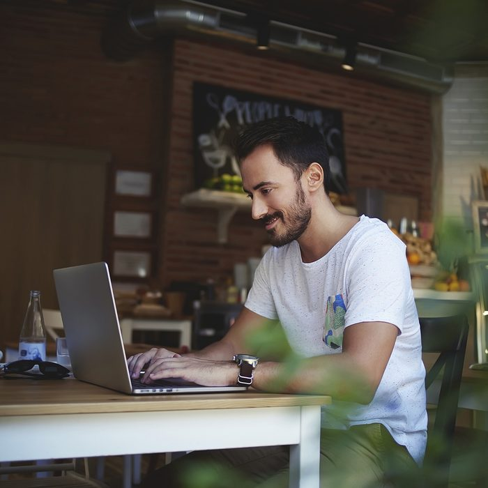 Smiling Caucasian man rewriting in social network with his friend via laptop computer while resting in bakery store, happy male student writing text on net-book during breakfast in modern coffee shop