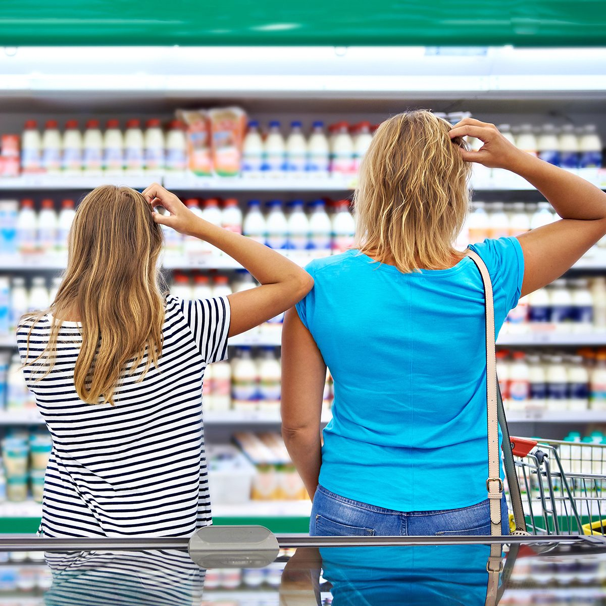 Mother and children are choosing dairy products in shop