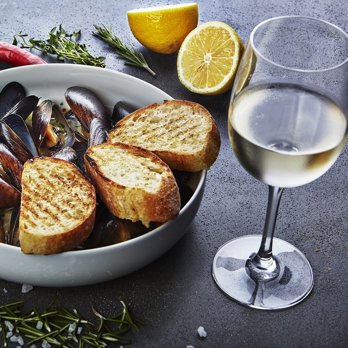 mussels in white wine sauce with glass of white wine white bread toasts