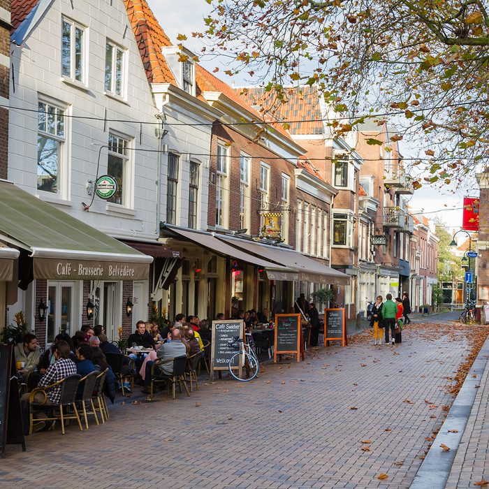People sitting at outdoors restaurant in the main square of Delf.