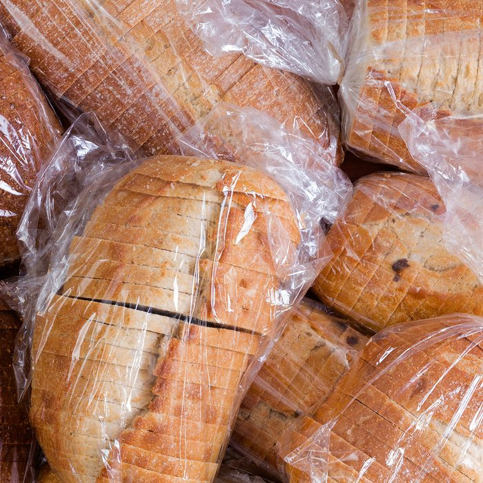 Plastic bags of assorted varieties of fresh sliced bread for a food drive piled on top of one another
