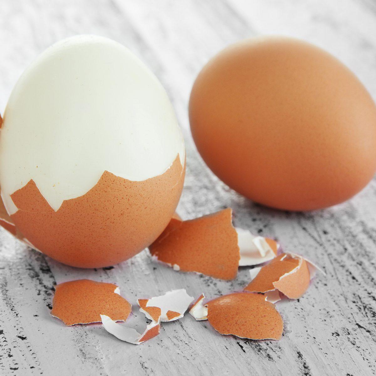 Peeled boiled egg on wooden background