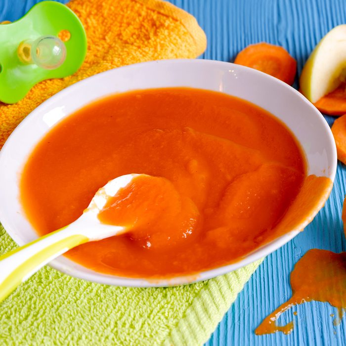 puree of baby carrot Apple on a wooden table spoon saucer white green pacifier napkin