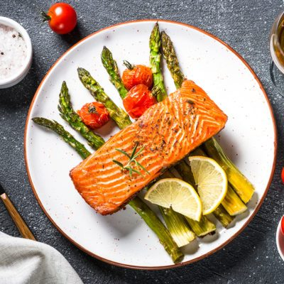 Baked salmon fish fillet with asparagus and tomato with glass wine on black stone table.