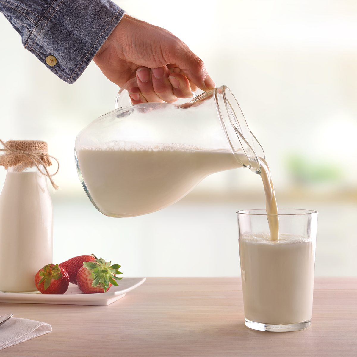 Serving breakfast milk with a jug in a glass on a white wooden kitchen table.