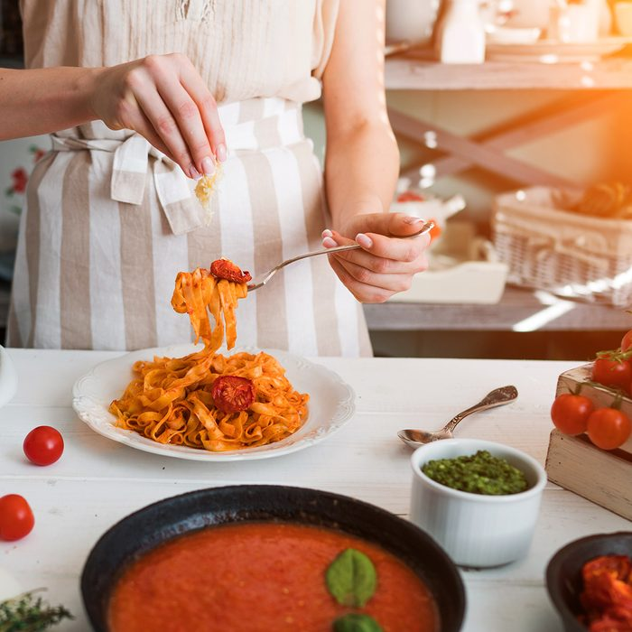 Italian style pasta dinner. Pasta with tomato and basil in plate on the wooden rustic table and ingredients for cooking. Chef hands preparing delicious pasta with tomato sous. Homemade food.; Shutterstock ID 1084753496; Job (TFH, TOH, RD, BNB, CWM, CM): Taste of Home