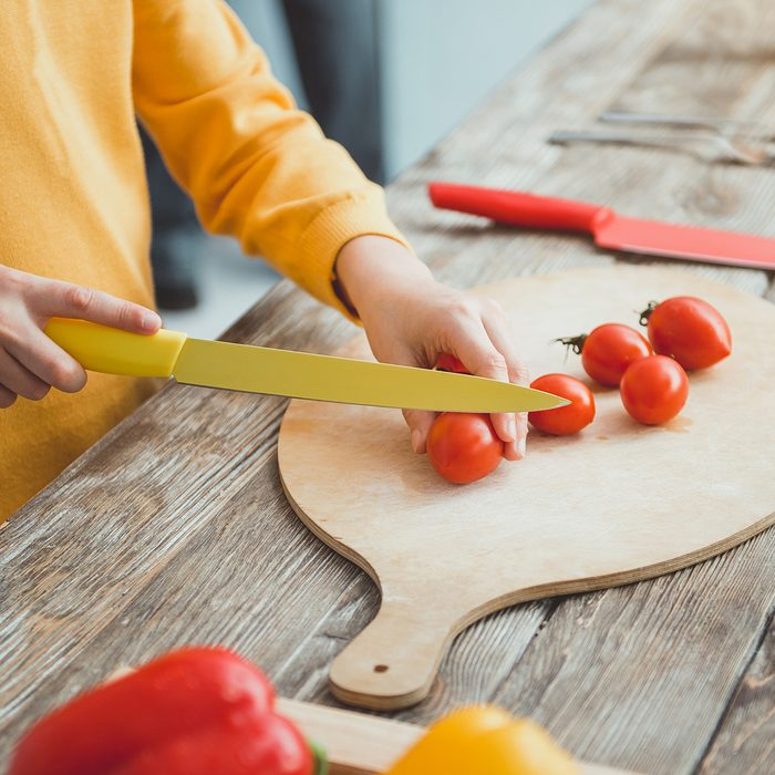 Close up of boy hands slicing vegetables for salad on cooking board; Shutterstock ID 1085667902; Job (TFH, TOH, RD, BNB, CWM, CM): Taste of Home
