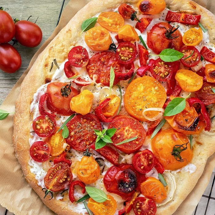 Oval pizza with yellow and red cherry tomatoes, ricotta cheese and basil on a wooden table.; Shutterstock ID 1193446483; Job (TFH, TOH, RD, BNB, CWM, CM): Taste of Home