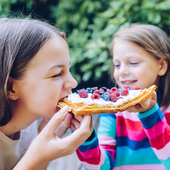 waffles - girls eating a waffle with whipped cream, raspberries and blueberries outdoors in the garden smiling and laughing; Shutterstock ID 1251984265; Job (TFH, TOH, RD, BNB, CWM, CM): Taste of Home