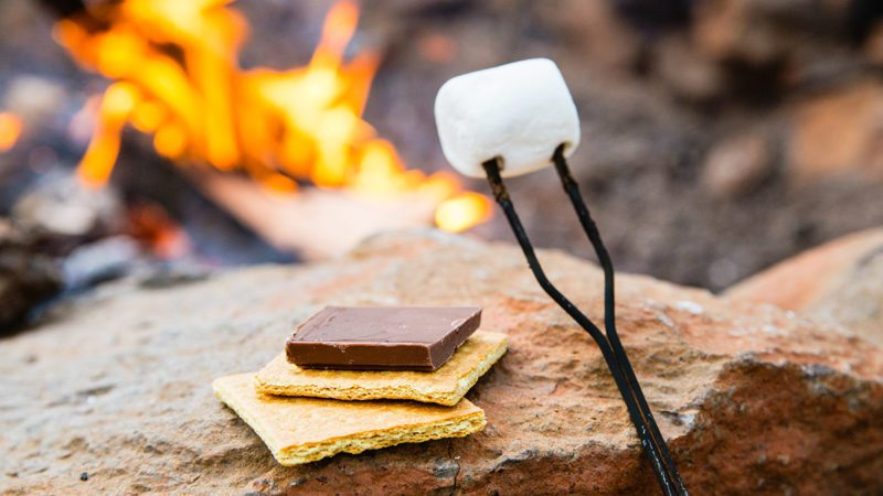 Graham crackers, chocolate, and marshmallow in front of a campfire ready to make s'mores.