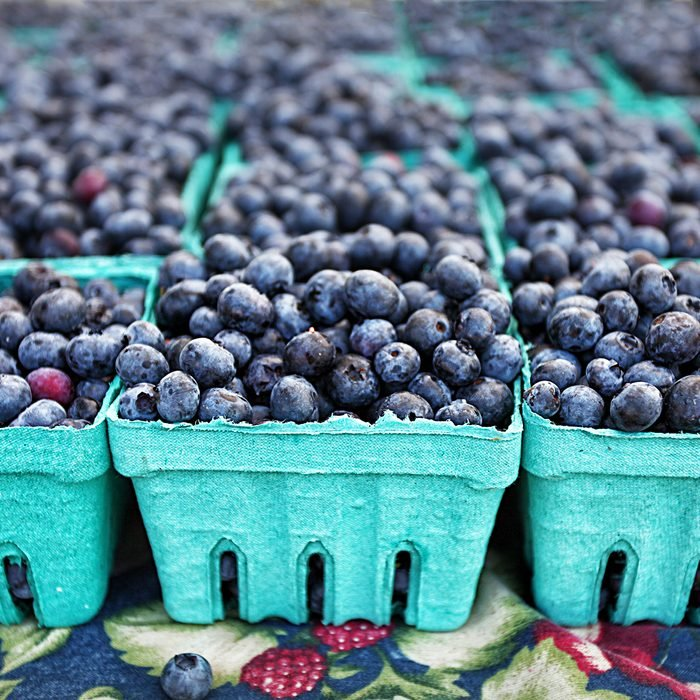 Blueberries in crates at farmers market farm fresh organic fruit in the summer for sale with depth of field; Shutterstock ID 393591292