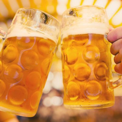 Two hands clinking beer glasses in octoberfest tent; Shutterstock ID 705089767; Job (TFH, TOH, RD, BNB, CWM, CM): Taste of Home