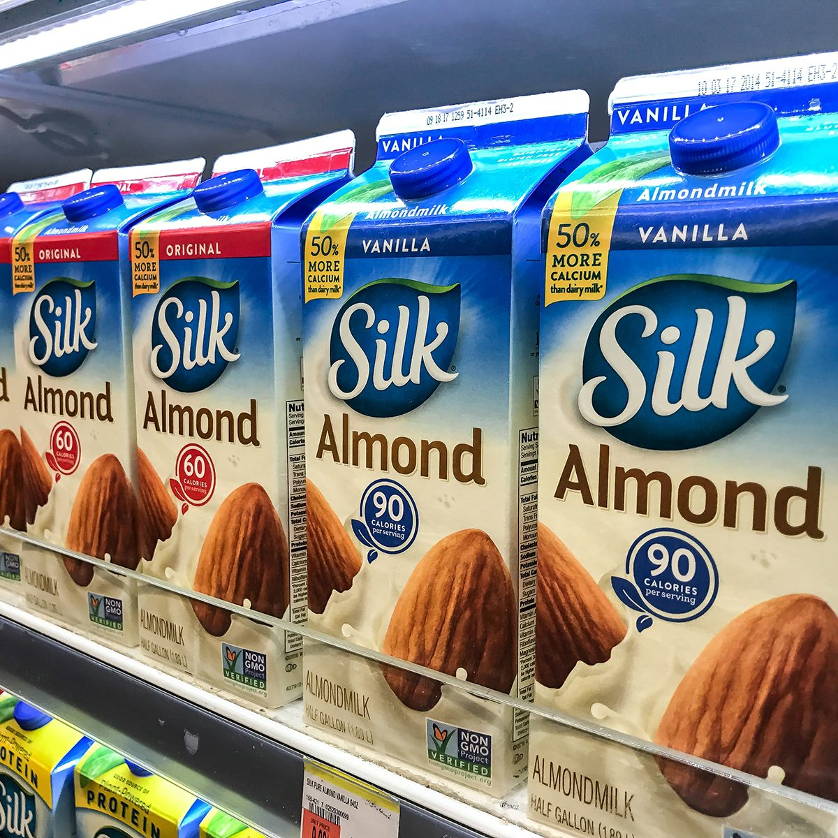 Cartons of almond milk stand on a shelf in a supermarket.