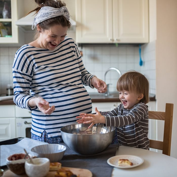 smiling young pregnant mother with dreadlocks is preparing in the kitchen with her son Toddler, dirty hands, make the dough for baking bread, lifestyle, toning, real interior
