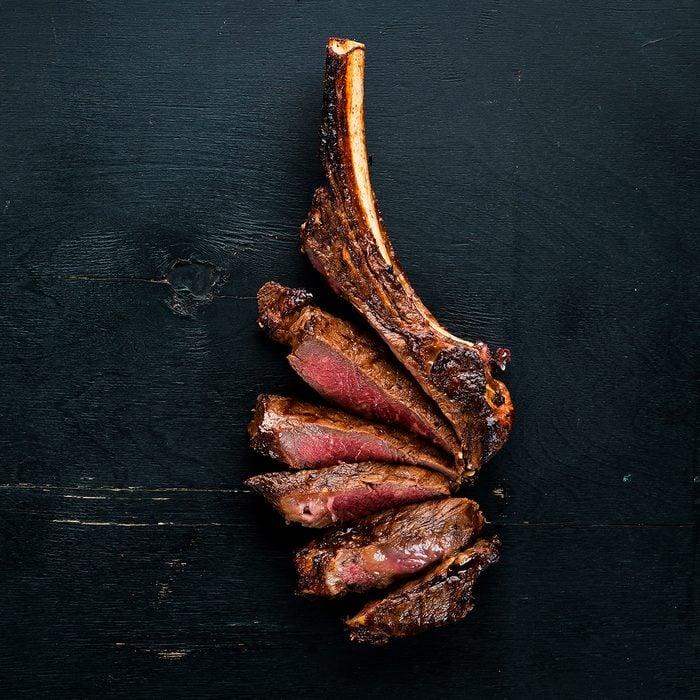 Steak on the bone. tomahawk steak On a black wooden background.