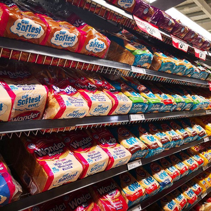 Interior view of Woolworths store shelf with bags of various brand breads.