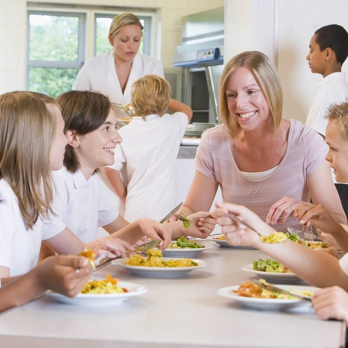 Students sitting at cafeteria table eating lunch with teacher