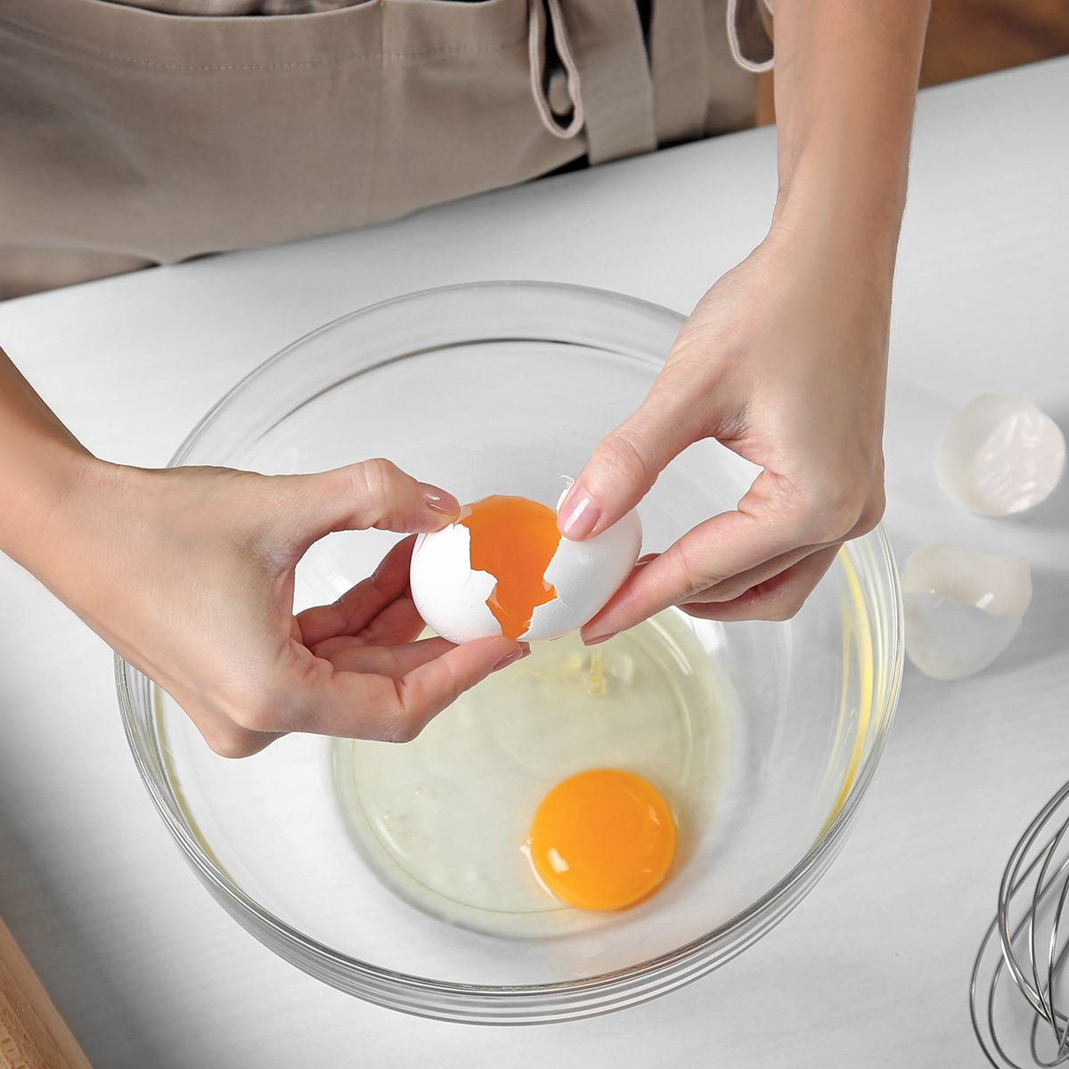Woman cracking eggs into glass bowl