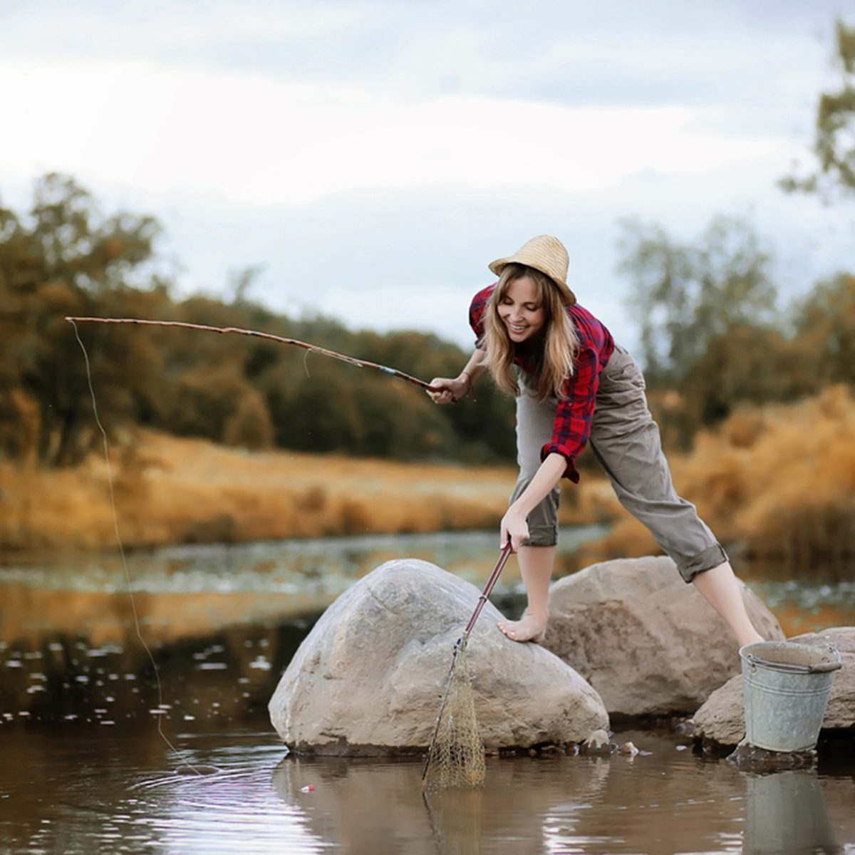 Beautiful young girl in autumn by the river with a fishing rod
