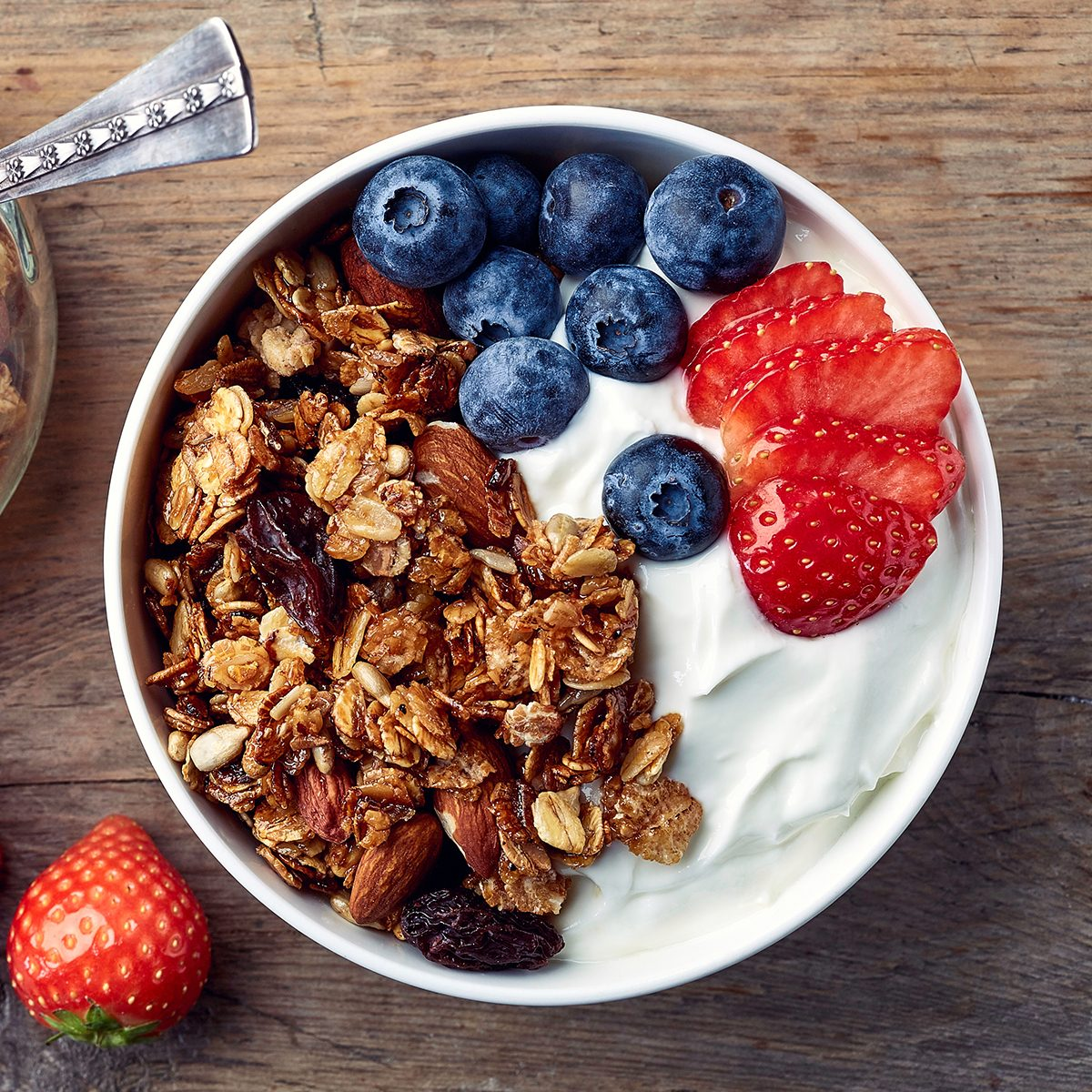 Bowl of homemade granola with yogurt and fresh berries on wooden background from top view; Shutterstock ID 521309641; Job (TFH, TOH, RD, BNB, CWM, CM): TOH