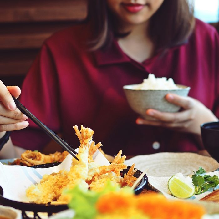 Young female hand using chopsticks to eat shrimp tempura with rice at restaurant.